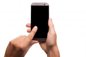 Hands holding up a cell phone with the screen turned off.