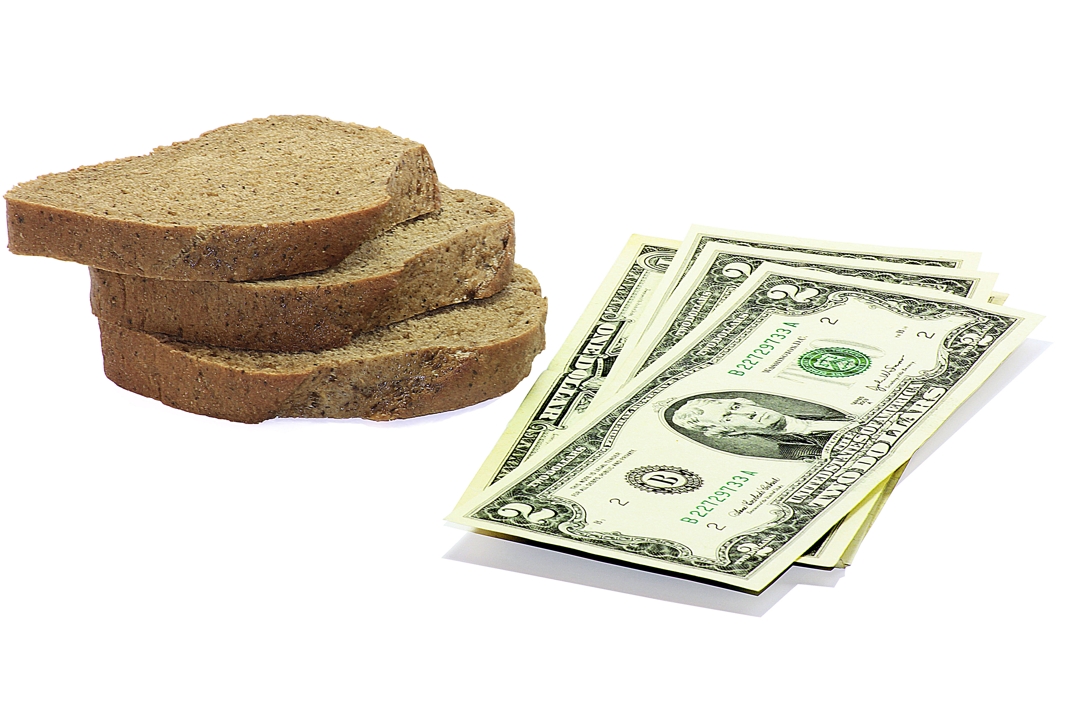 Slices of bread next to a stack of dollar bills.