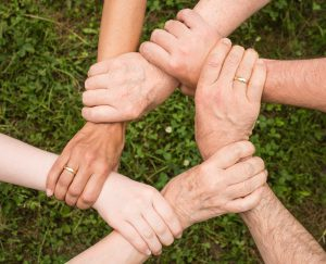 Six hands hold each other's wrists, forming a circle.