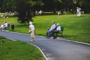 Seniors sitting on benches in a park and a woman walking in front of them.