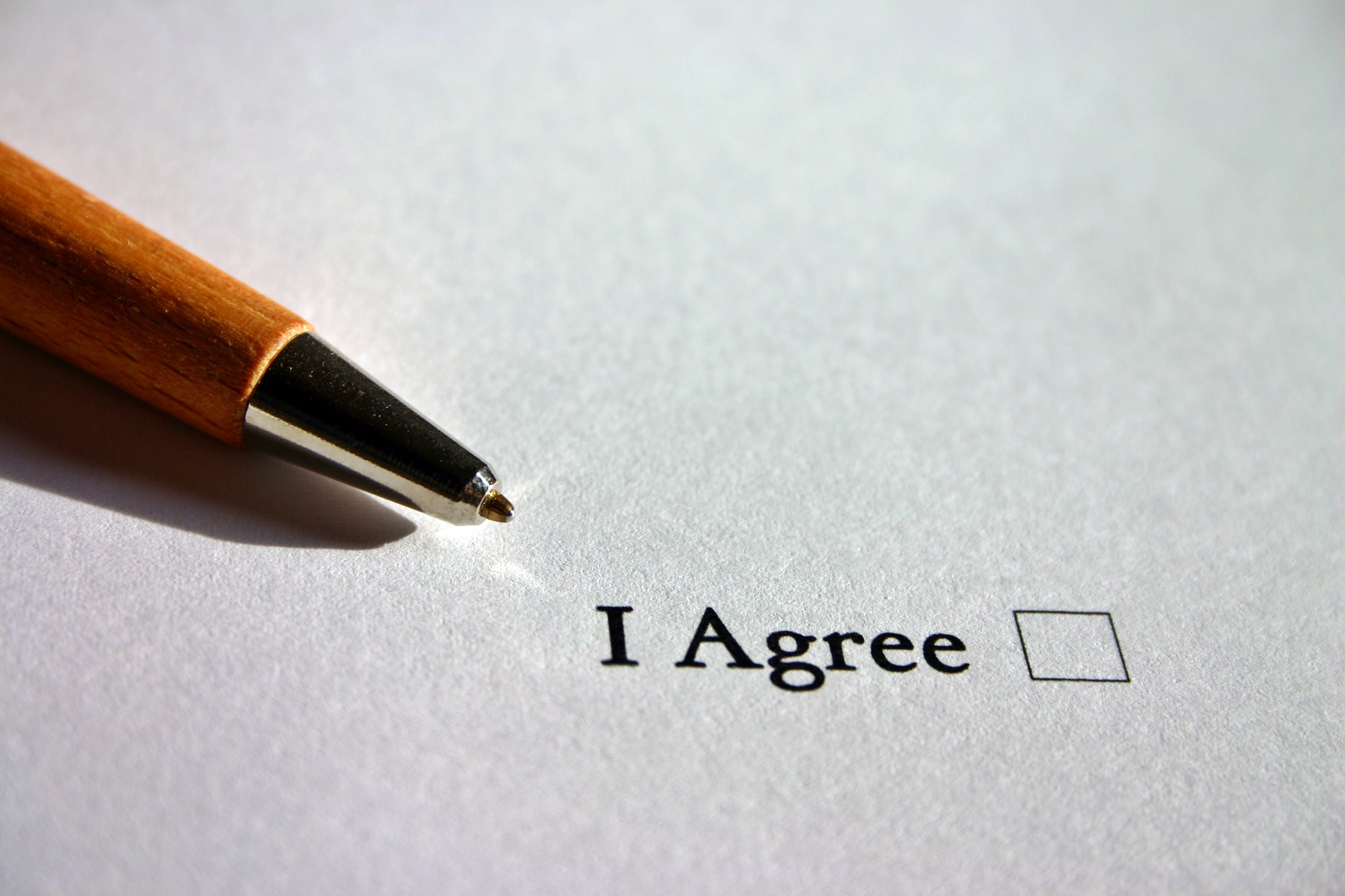 """Pen next to a check box stating """"I Agree""""."""